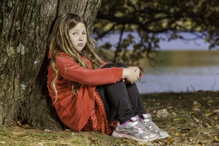 young girl, in red outfit leaning against a tree. A look of sadness or thought on her face, vlose up full body shot with lake in the background blurred.