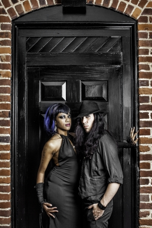 Interracial gothic couple standing in front of a large black door surrounded by bricks.