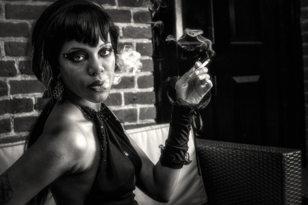 Sexy african american gothic woman smoking. Creative, dramatic lighting with smoke, sexy eyes, seductive look, black and white photo photo
