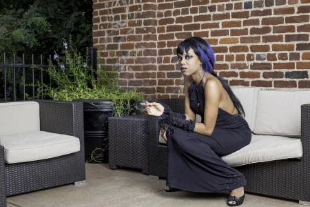 Sexy african american gothic woman smoking. Sitting on a couch outddor patio, spce for text. Stock Photo - 17539239