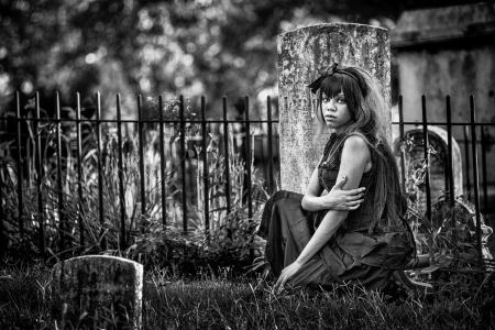 Beautiful african american gothic woman in a graveyard. Black and white photo with added film grain. Moody photo expressing depression, loneliness, abadnonment and more. Very old cemetery.