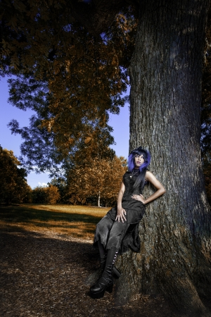 Beautiful african american gothic woman leaning against a large tree. Beautiful, vibrant fall like colors surrounding her.  photo
