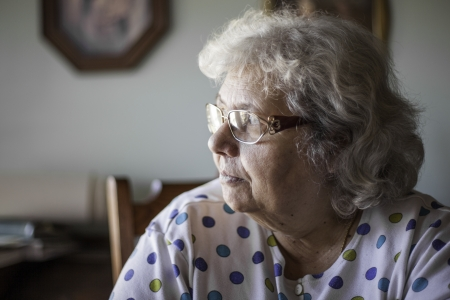elderly woman in natural setting in the home. Shallow depth of field blurring the background. Look of thought or a feeling of lonliness.  Stock Photo