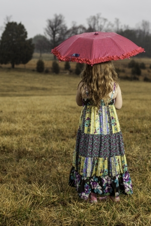 young girl holding an umbrella in the rain looking out at a field photo