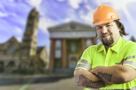 City construction worker arms crossed, tattooed with blurred city buildings behind him Stock Photo - 17539286