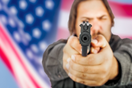 White male holding a handgun with the american flag as a backdrop Stock Photo - 17539280