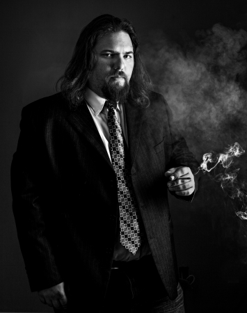 modern looking white man with long hair wearing a sport coat and tie smoking a cigarette. Dramatic lighting showing the smoke shot in black and white.  photo