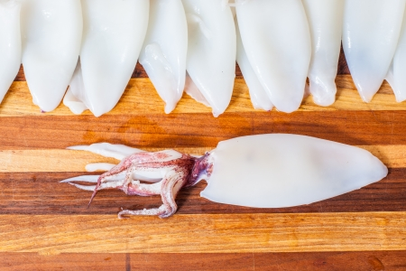Fresh cleaned squid laying out on a cutting board ready to be prepared