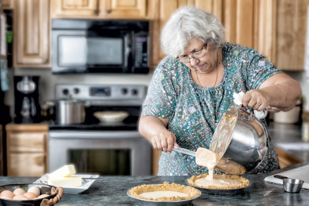 Photo of a grandmother elderly active woman in a natural kitchen filling pies. White older woman in the kitchen baking.