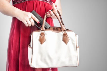 White woman in a red dress removing a small handgun from her purse photo