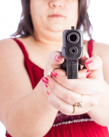 white hispanic woman holding a handgun pointed at the screen Stock Photo