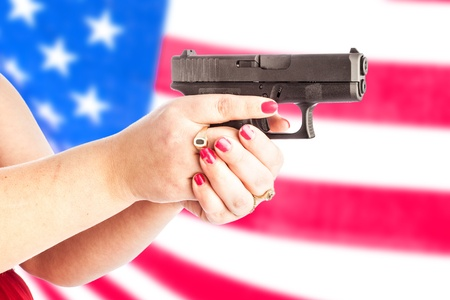 Womans hands holding a  small handgun with an american flag blurred as the background