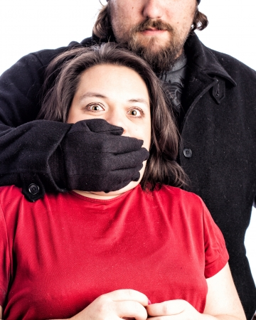 attacker: Isolated photo of a woman in red shirt being assaulted from behind by a white male in a black coat, hat and gloves. The mans hand is covering the womans mouth with fear in her eyes.
