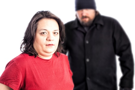 attacker: Isolated photo of a woman in red shirt being assaulted from behind by a white male in a black coat, hat and gloves. The man is blurred out of focus behind the woman  Stock Photo