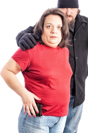 Isolated photo of a woman in red shirt being assaulted from behind by a white male in a black coat, hat and gloves. Man with his hand on a womans shoulder and her reaching for her gun in her jeans pocket