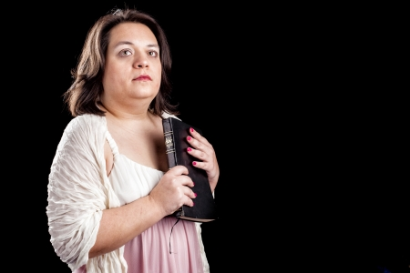 hispanic looking woman in a light dress against a black background holding a bible photo