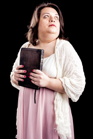 hispanic looking woman in a light dress against a black background holding a bible close to her body as she looks up in thought.  photo