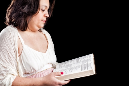 hispanic looking woman in a light dress against a black background holding a bible open as she reads it photo