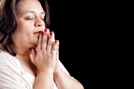 meditation help: Hispanic woman with her hands folded in prayer and eyes closed agains a black background with space for custom text
