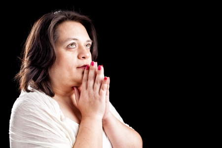 Hispanic woman with her hands folded in prayer and eyes open agains a black background with space for custom text photo