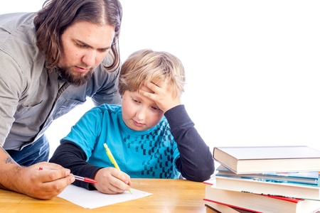 father leaning over to help son work one home work. Sitting at a desk with papers and books isolated on white with space for custom text Stock Photo - 17539254