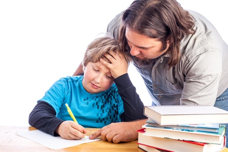 father leaning over to help son work one home work. Sitting at a desk with papers and books isolated on white with space for custom text Stock Photo - 17539263