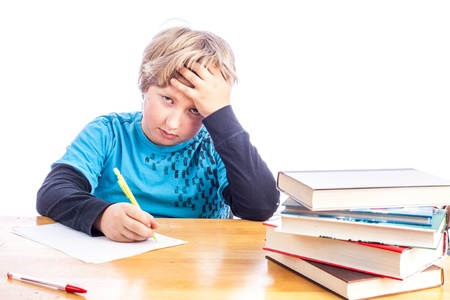 Young boy at a desk hand on his head frustrated doing homework