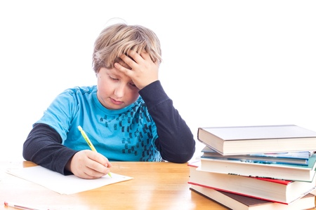 Young boy at a desk hand on his head frustrated doing homework photo