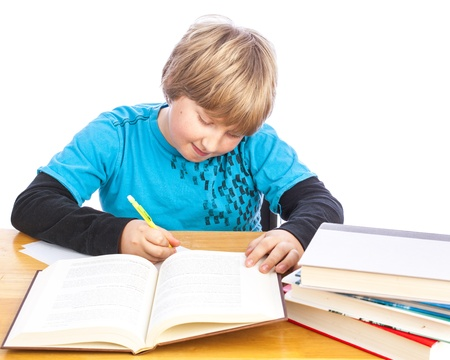 learning by doing: isolated young boy at a table doing homework with books