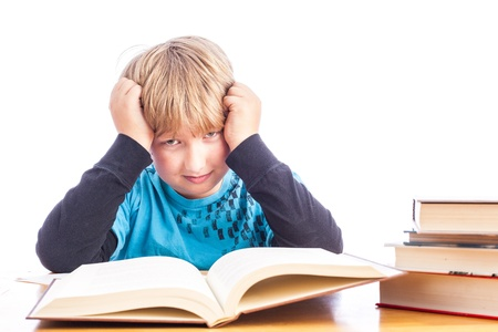 isolated young boy at a table doing homework with books. Space for custom text photo
