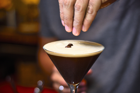 bartender adding coffee grains in espresso martini