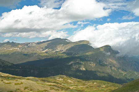 mountaintops: Clouds roll off the mountaintops of the Rocky Mountains  Stock Photo