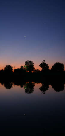crescent lake: A lake reflects the morning planets of Venus, Jupiter, and the crescent moon