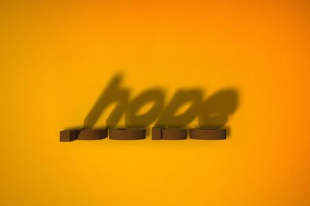 Words on a yellow background. HOPE blocks and shadows.