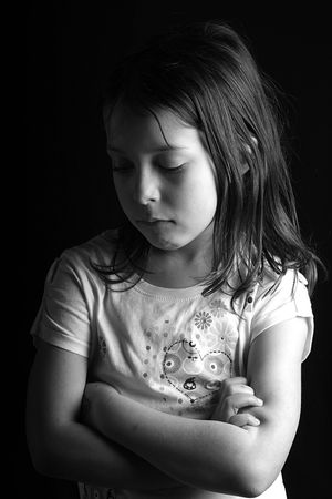 seven year old: Shot of a pretty seven year old girl looking down with her arms crossed, against a black background II