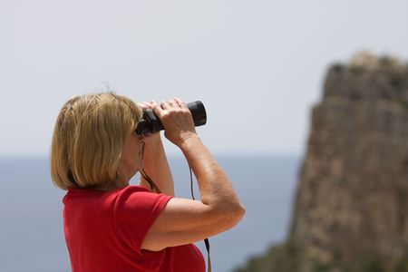 Shot of a senior woman looking through binoculars photo