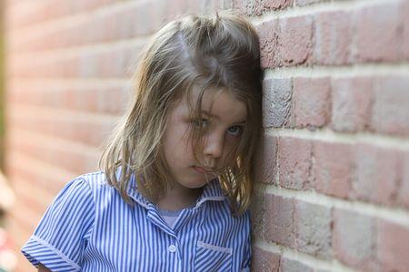 occhi tristi: Tiro di un triste giovane ragazza bionda contro il muro di mattoni  Archivio Fotografico