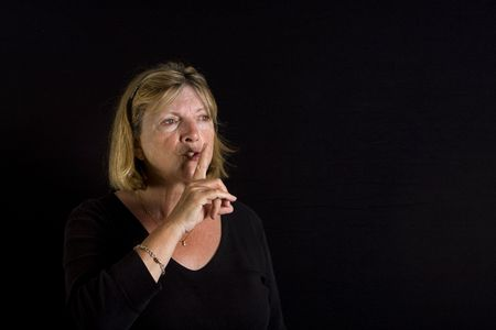 sh: Shot of a Senior Lady going Shhhh against a Black Background Stock Photo