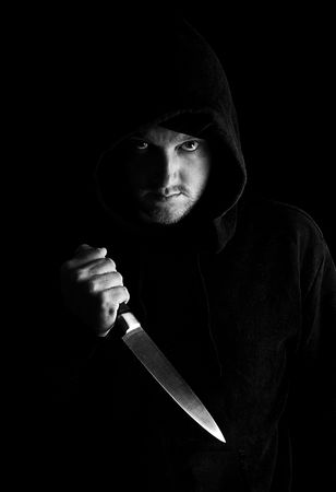 menacing: Shot of a Menacing Male in Hooded Top clutching a Large Kitchen Knife