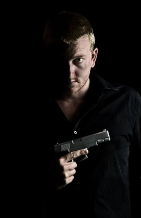 menacing: Intimidating Male Holding a Gun to his Chest Stock Photo