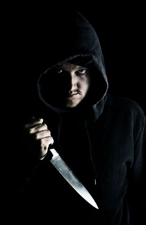 Intimidating Hooded Youth Clutching Knife to Chest photo