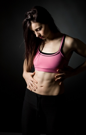 Shot of a Sporty Female Holding her Stomach