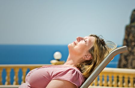Shot of a Senior Lady Sunbathing against Coastal Backdrop Stock Photo