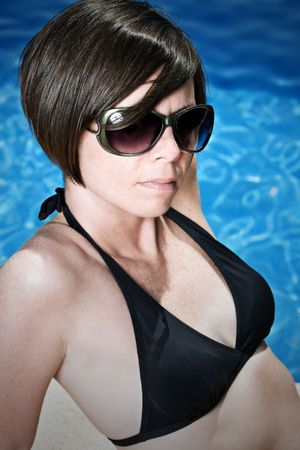 Shot of a Pretty Brunette Girl in Sunglasses by the Pool Stock Photo