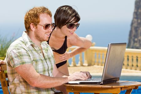Young Couple Looking at their Laptop Whilst on Holiday photo