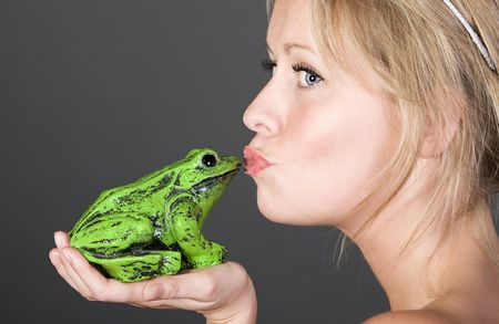Shot of a Pretty Blonde Girl Kissing a Frog Stock Photo