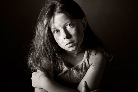 homeless children: Low Key Black and White Shot of a Scared and Filthy Brown Haired Child Stock Photo