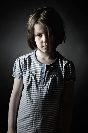 Low Key Shot of a Sad Little Girl against Grey Background Stock Photo