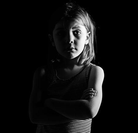 petite fille triste: Low Key Shot d'un jeune enfant avec les bras crois�s Banque d'images
