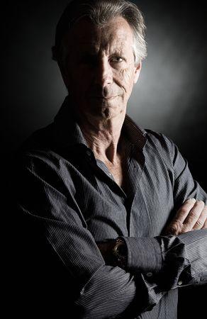 Low Key Shot of a Handsome Senior Man against Dark Background photo